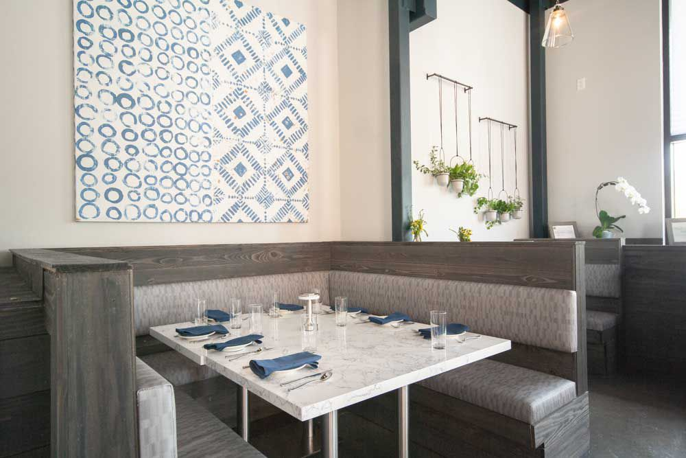 A banquette at Roots Southern Table. The seating is grey with light grey accent fabric, the table is white and set with blue linens, silverware, glasses, and white plates
