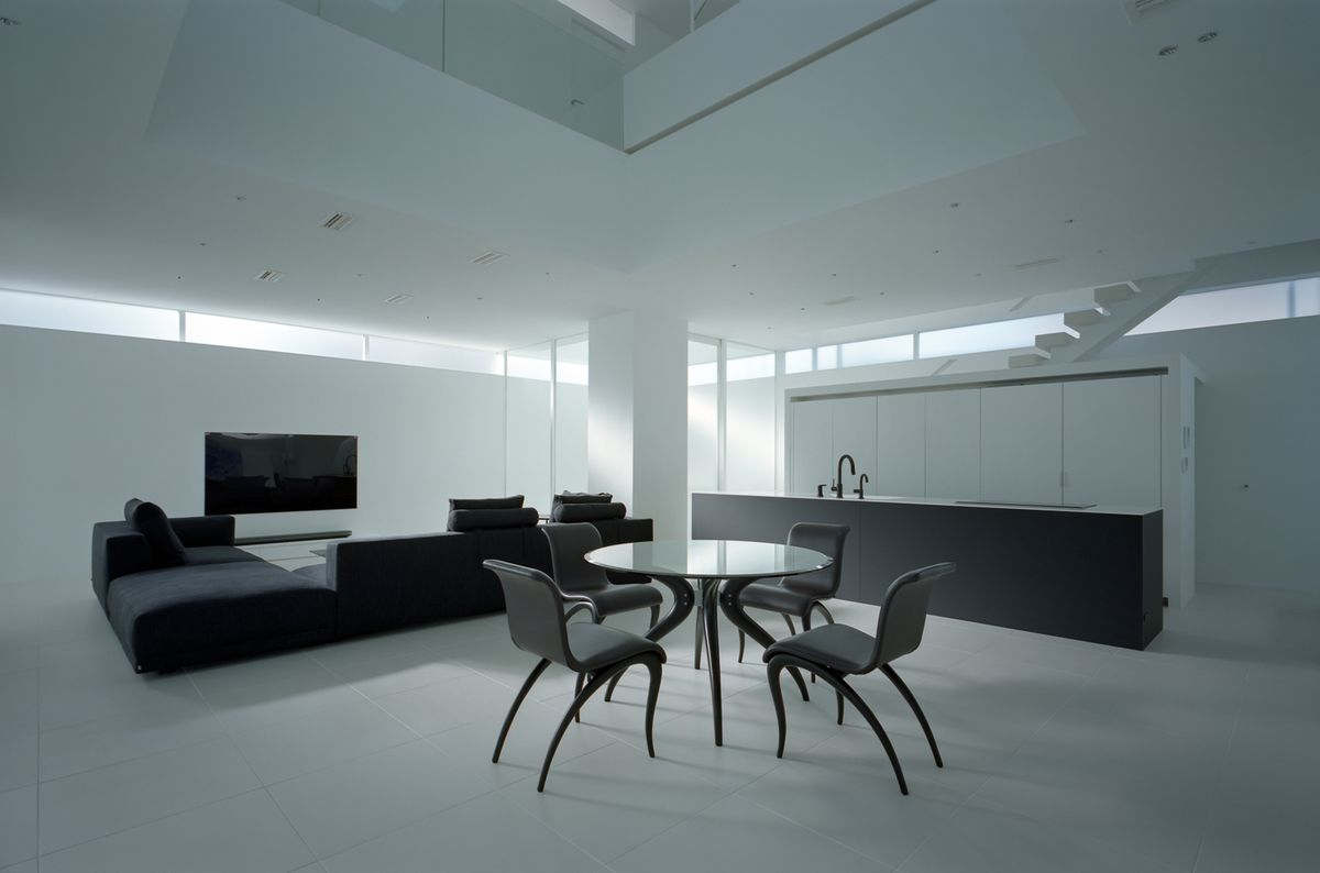 Modern living room with stark white walls and black furniture.