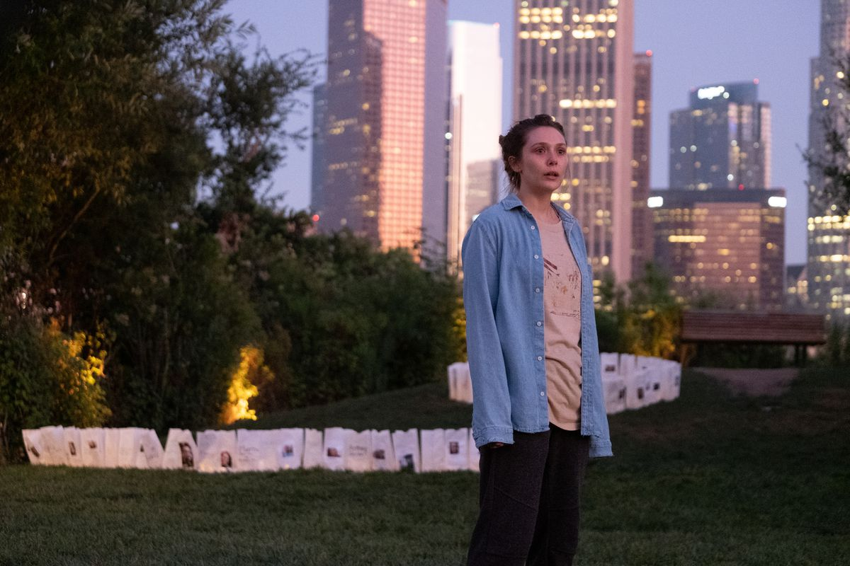 """Leigh, the main character in the TV show """"Sorry for Your Loss,"""" goes on a sunset walk in a park with downtown Los Angeles behind her."""