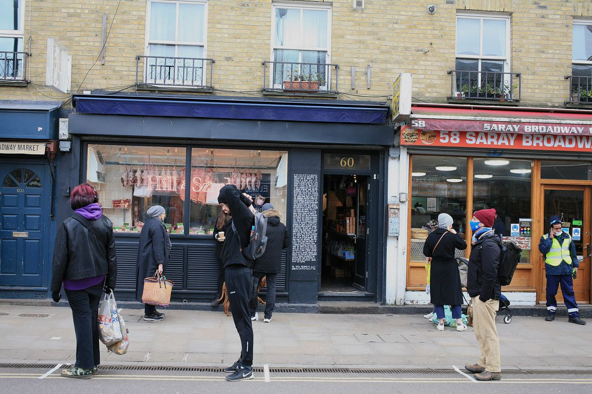 Hill and Szrok on Broadway Market during lockdown, with people queuing outside in the middle of the coronavirus pandemic in hackney, east London