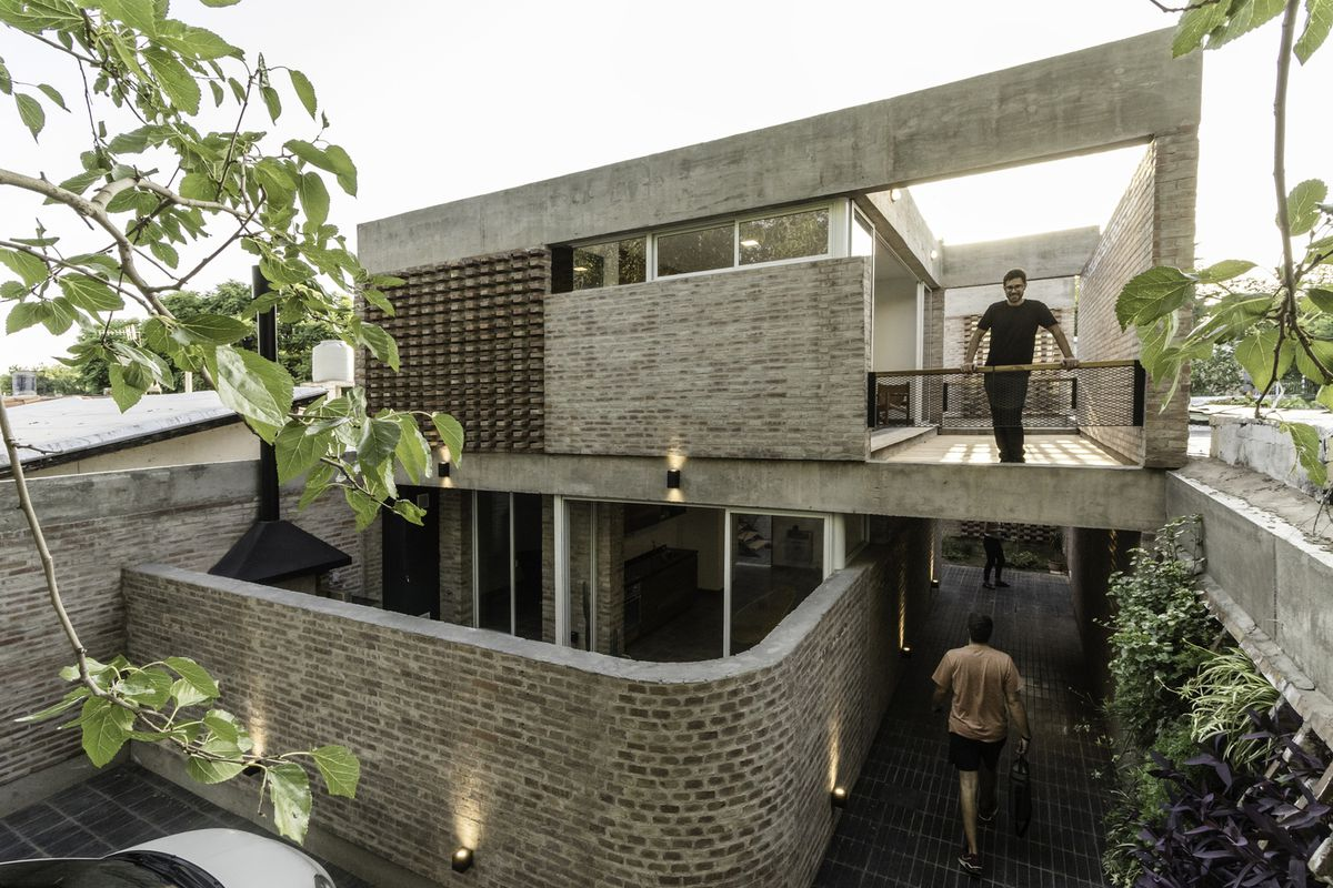 Man standing on terrace of brick clad building.