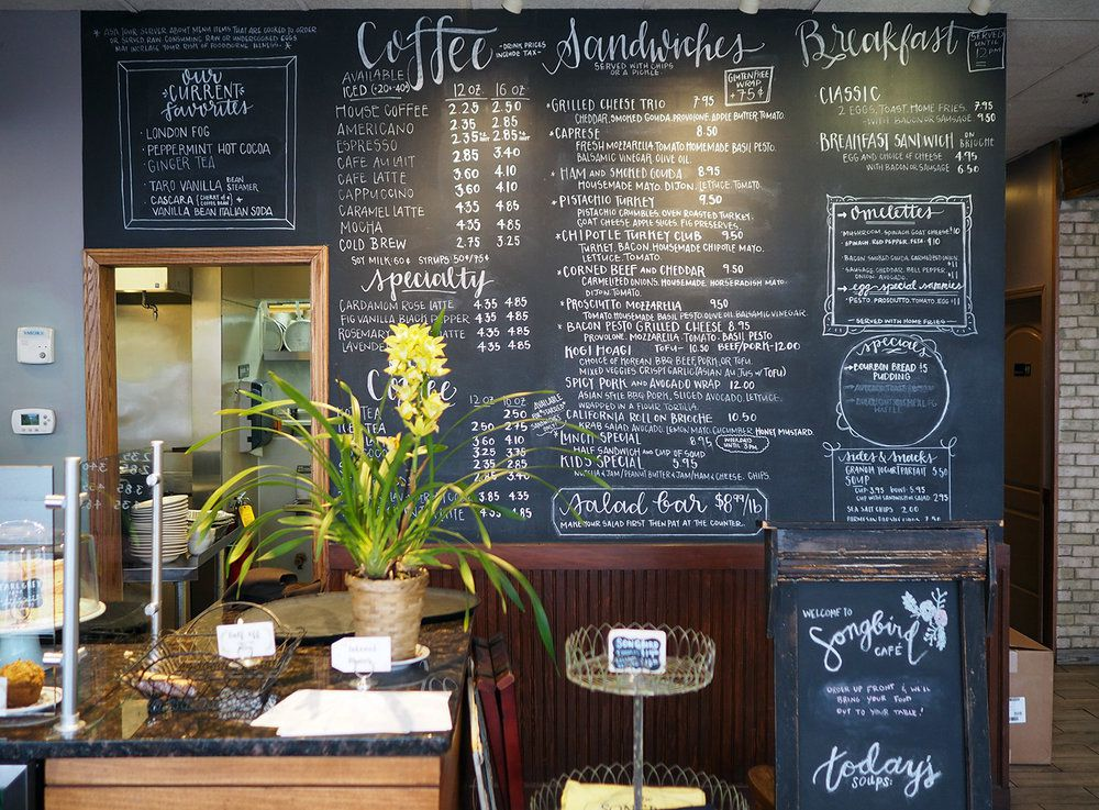 A blackboard menu is on the wall next to a counter with a flowering potted plant on it.