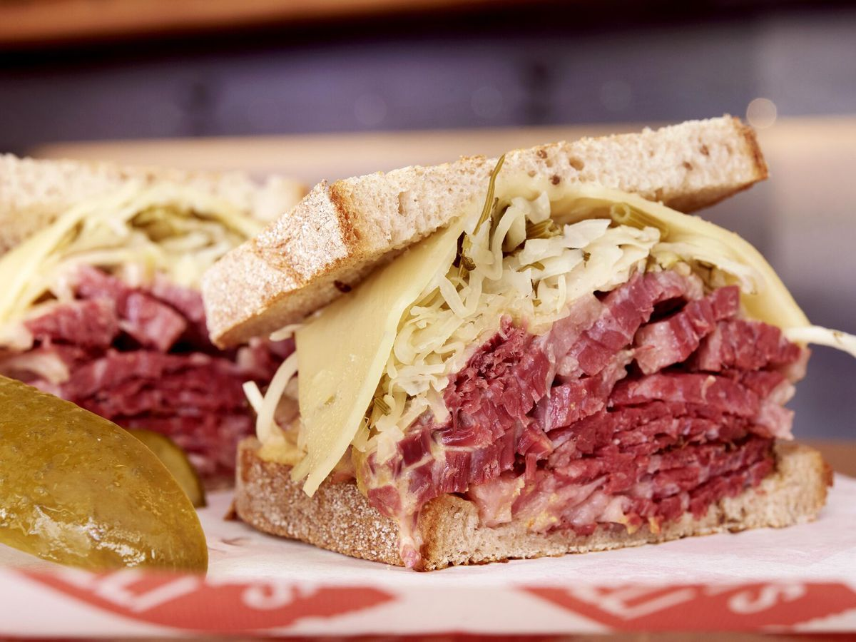 A Montys Deli reuben sandwich, white bread stuffed with pastrami, cheese, sauerkraut and pickles