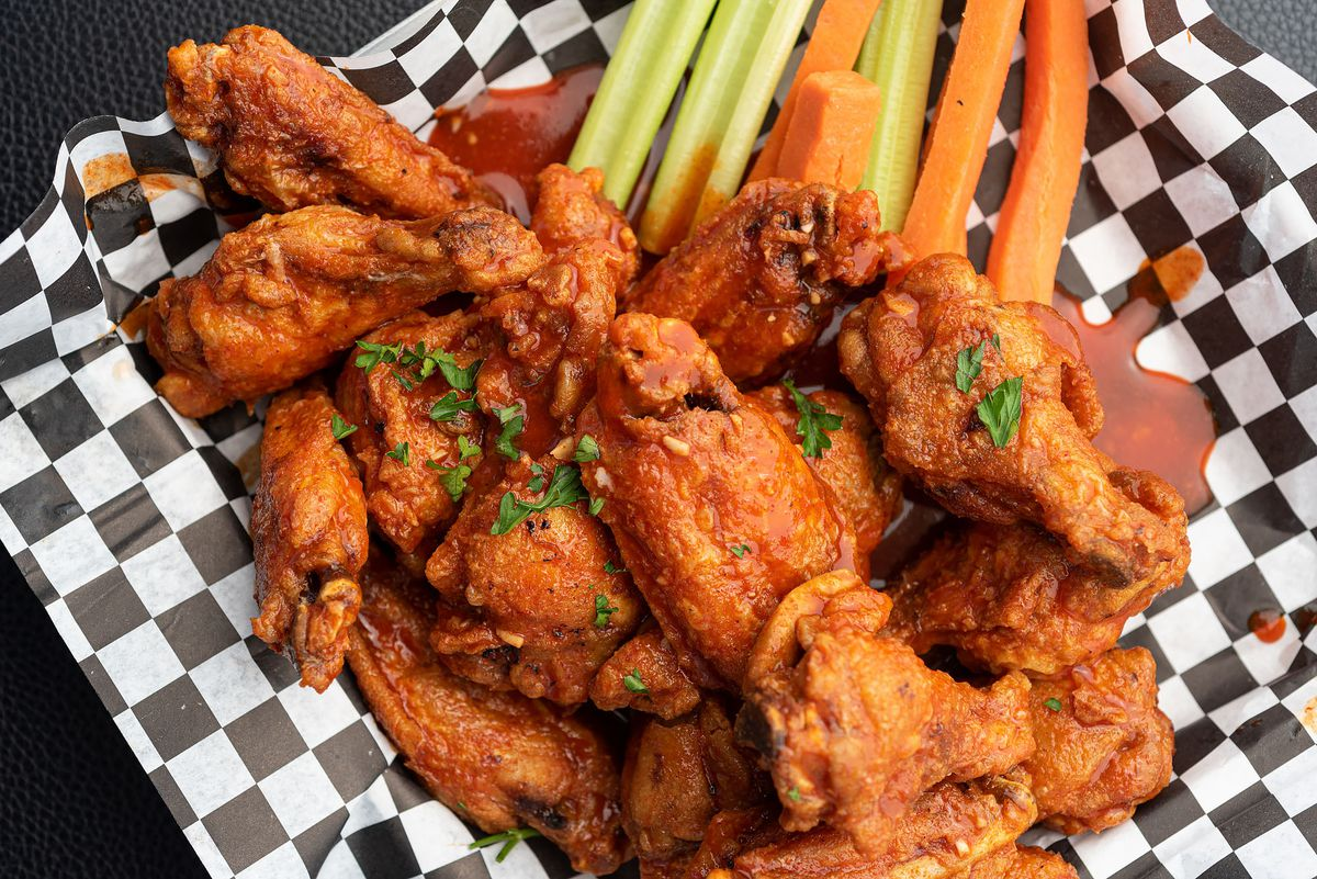 Sauced chicken wings with carrots and celery sticks on a checkered basket.