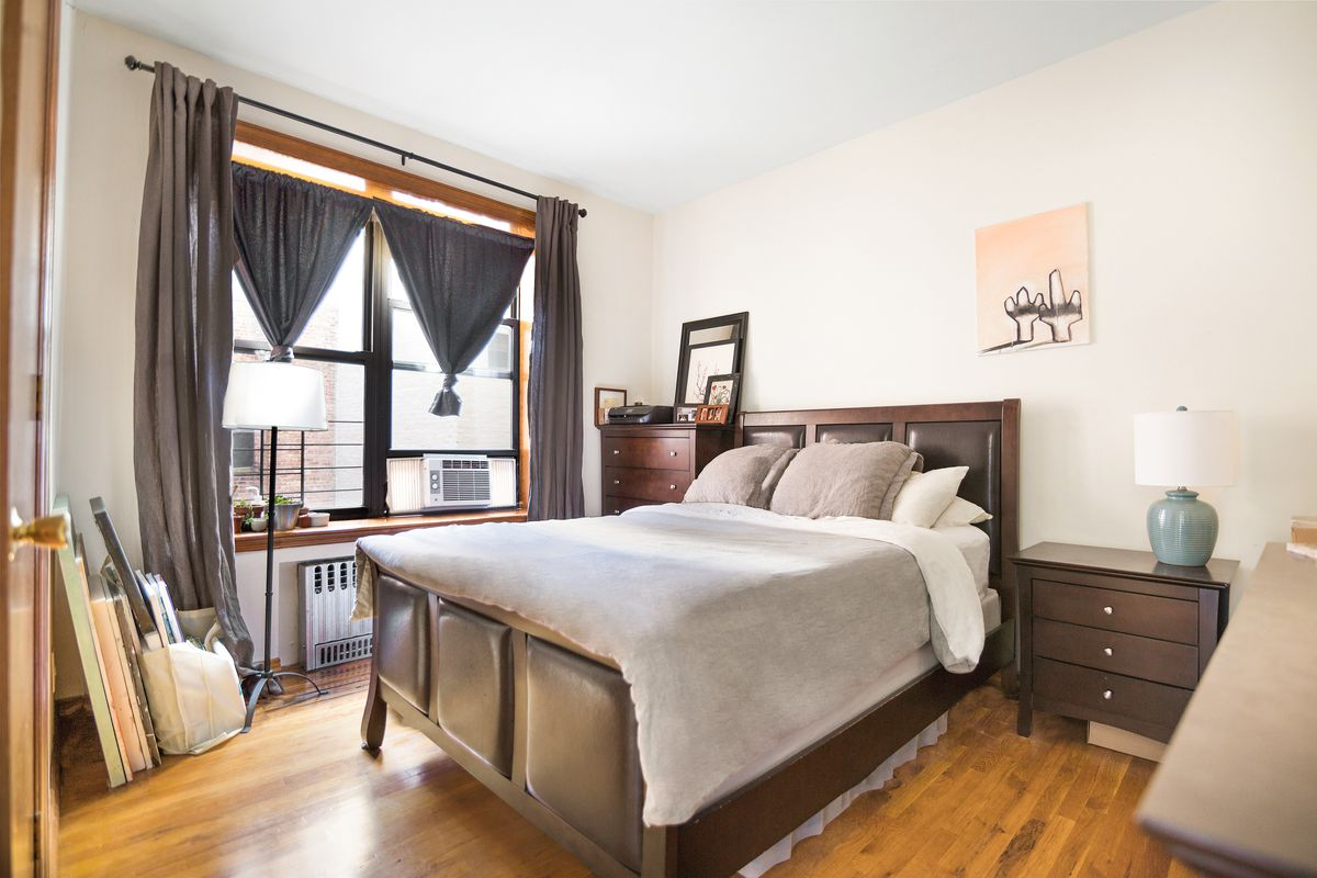 A bedroom with a medium-sized bed, hardwood floors, wooden furniture, and a large window with dark grey curtains.