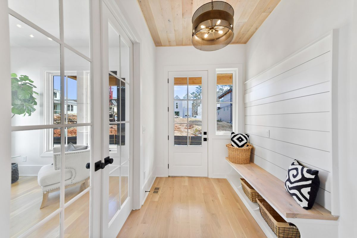 Foyer with white walls, light wood ceiling and floors, and built-in storage with bench.