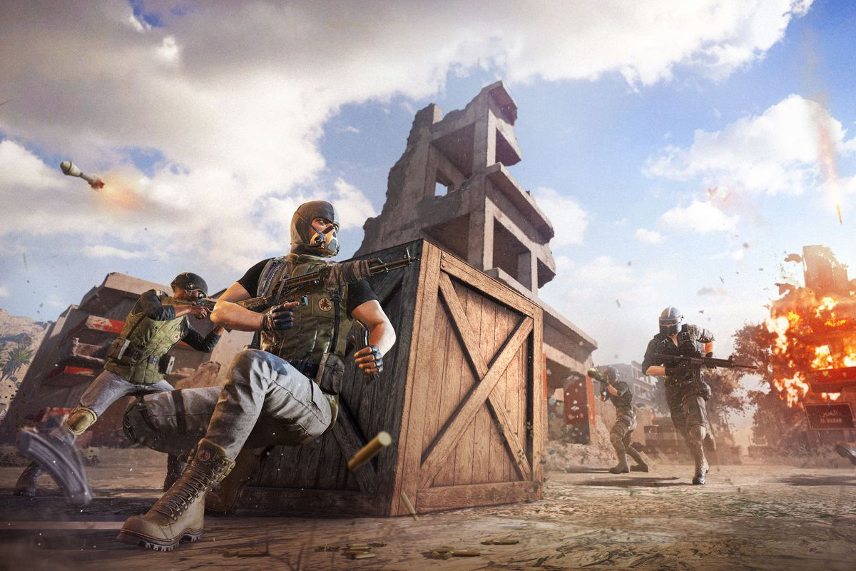 Two PUBG players crouch behind boxes as two more players rush toward them with explosions in the background.