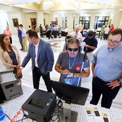 Nick Rios, center, who is visually impaired, tries out Clear Ballot's voting system as the company's Chris Hanna, right, looks on at the state Capitol in Salt Lake City on Wednesday, Aug. 2, 2017. Members of the public will be able to try out five different machines the state is considering buying.