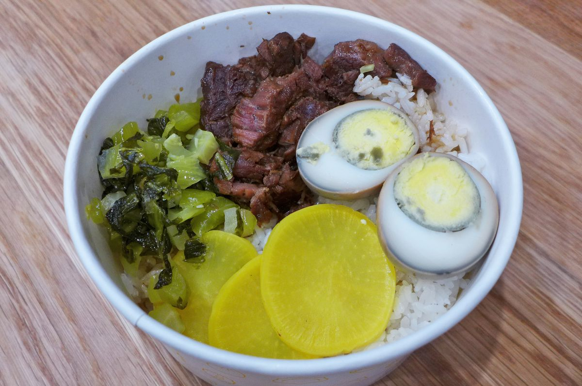 A bowl contains rice topped with beef, green mustard greens, a boiled egg cut in half, and yellow pickled radish...