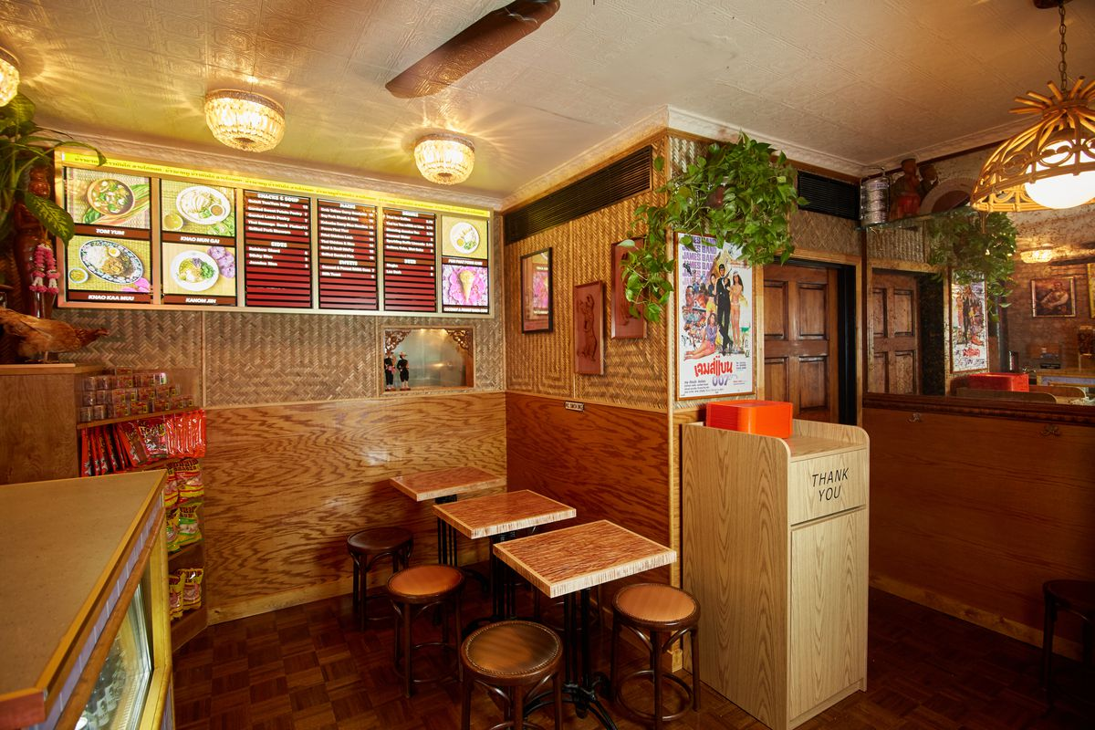 A petite dining room with three small wooden tables and wooden stools, plus a menu board with Thai dishes.