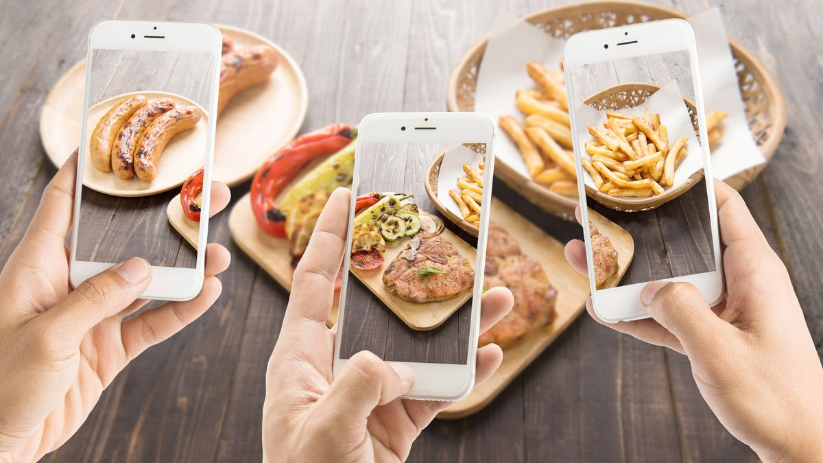 stock photo of people taking phone photos of food