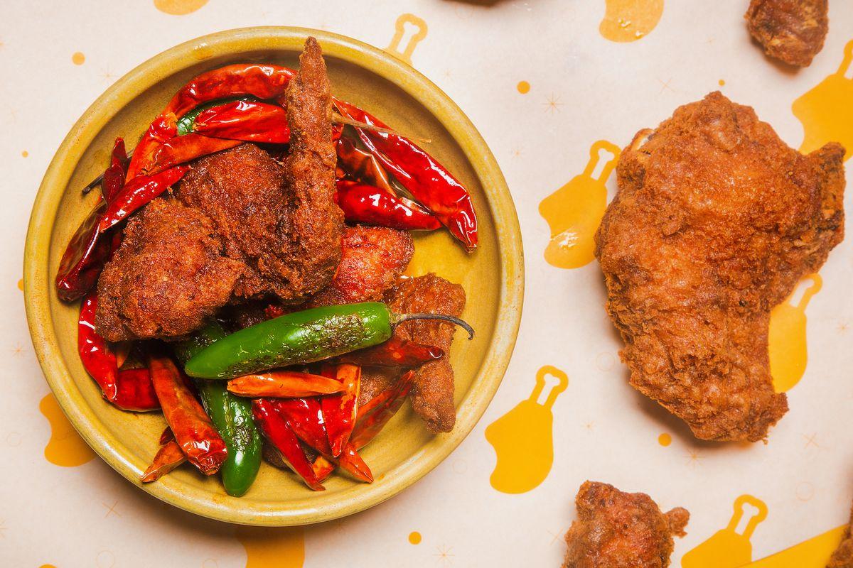 一个黄色的盘子里放着炸鸡翅和很多辣椒。