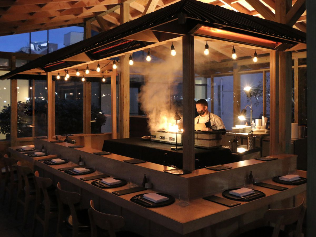 Sushi restaurant Chikarashi Isso's heated outdoor dining structure with a chef cooking in the center