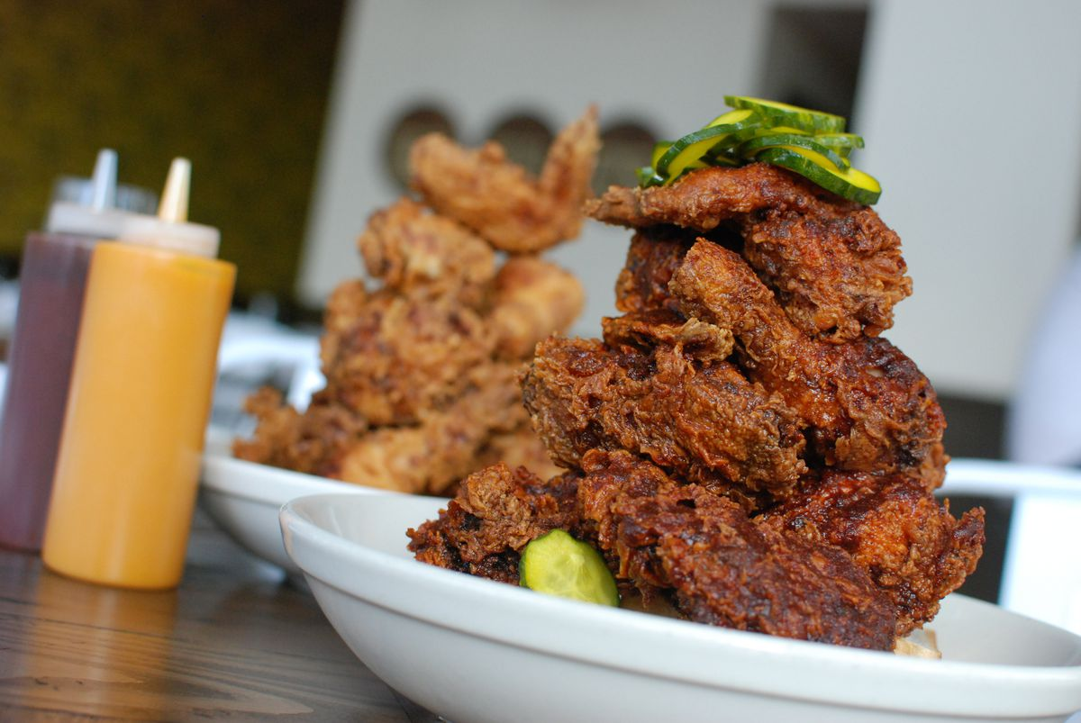 Two tipping bowls of towering fried chicken, one in blaze orange hot sauce