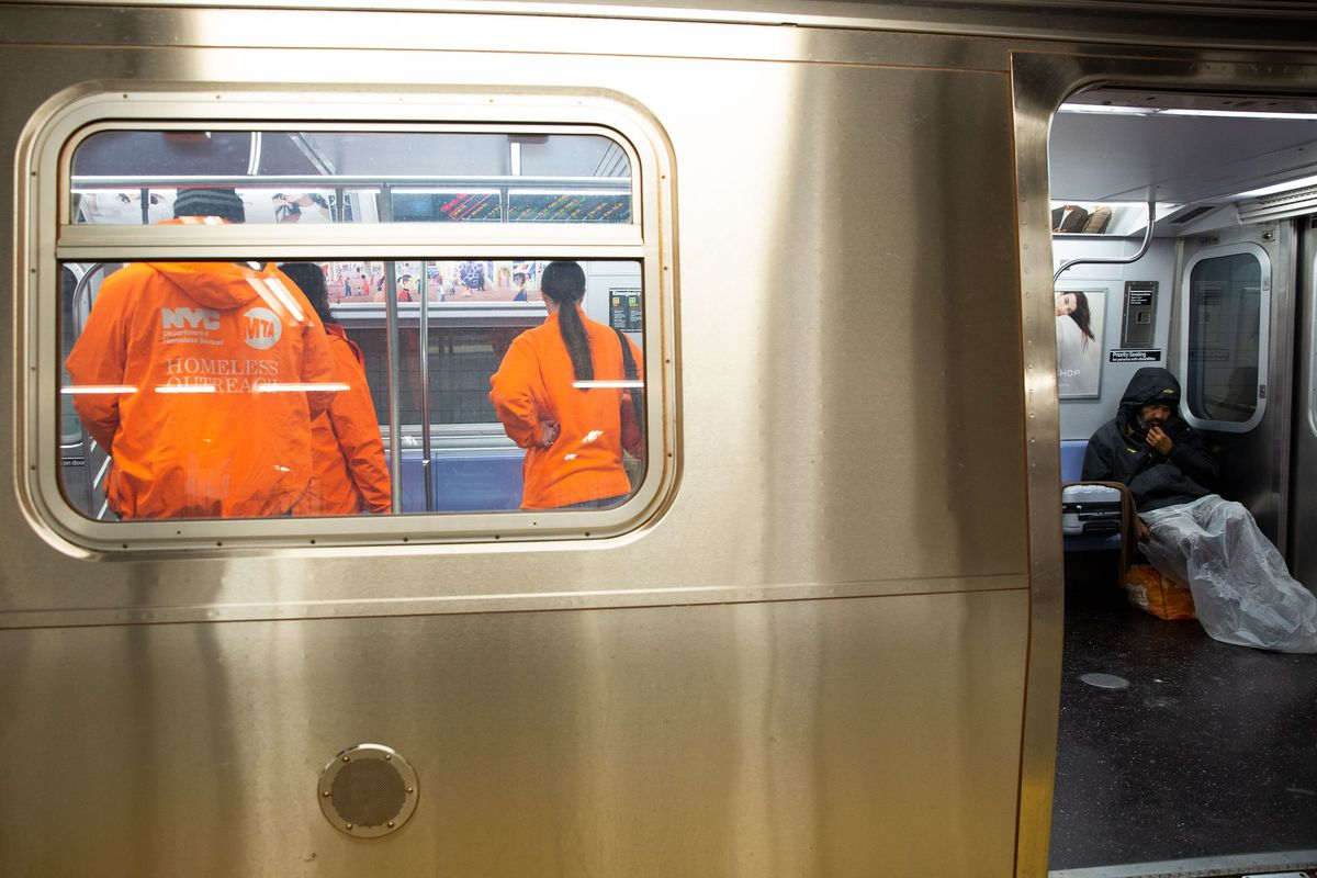 Homeless outreach workers speak to people sleeping on an E train at the World Trade Center stop.