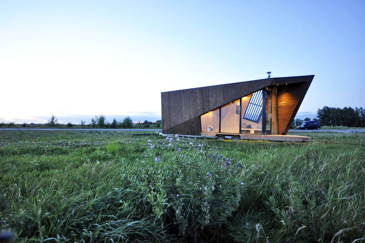 Angular tiny house sitting in field at dusk.