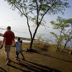 St.George native Jeremy Johnson walks with children as he tours a village near the Haitian and Dominican Republic border on Sunday, Jan., 24, 2010.
