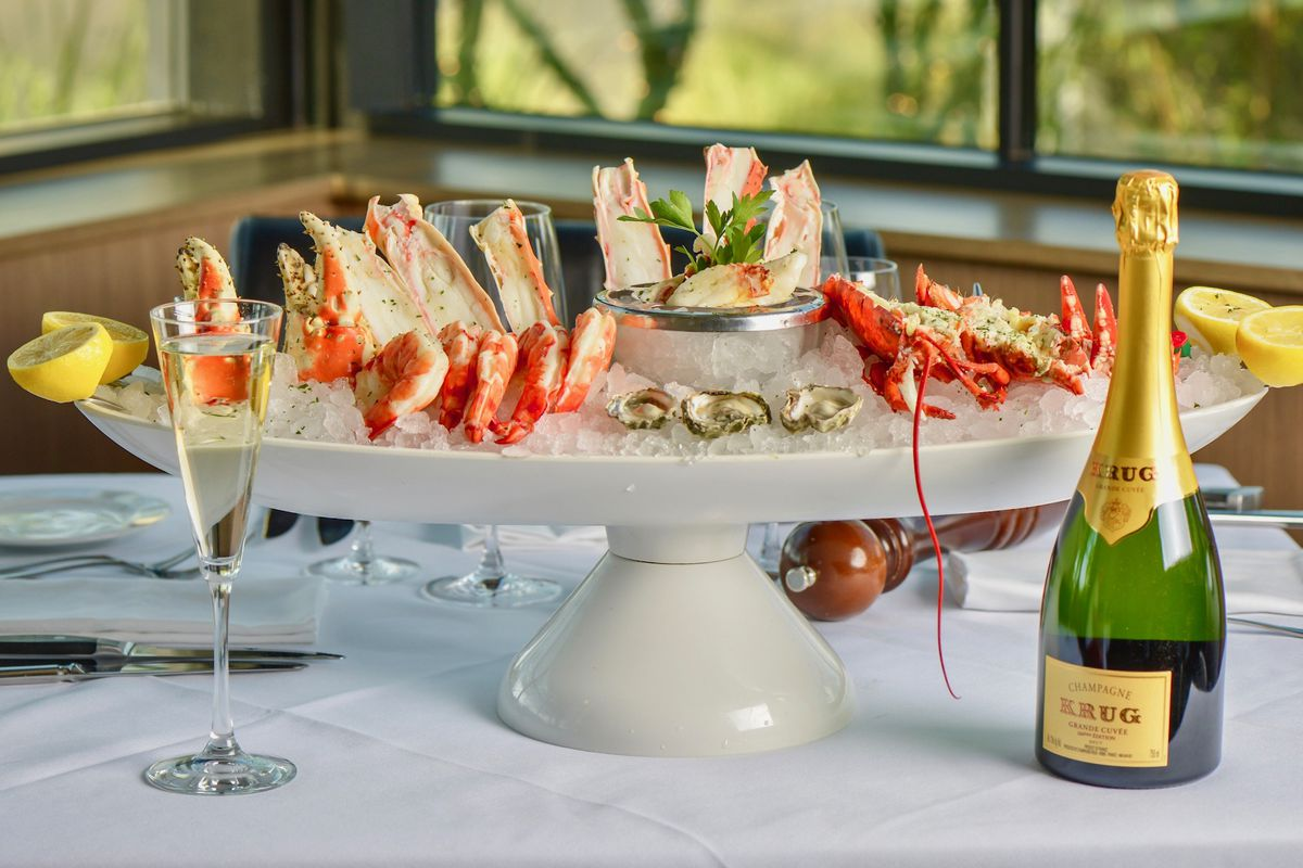 platter with seafood on ice and bottle of champagne