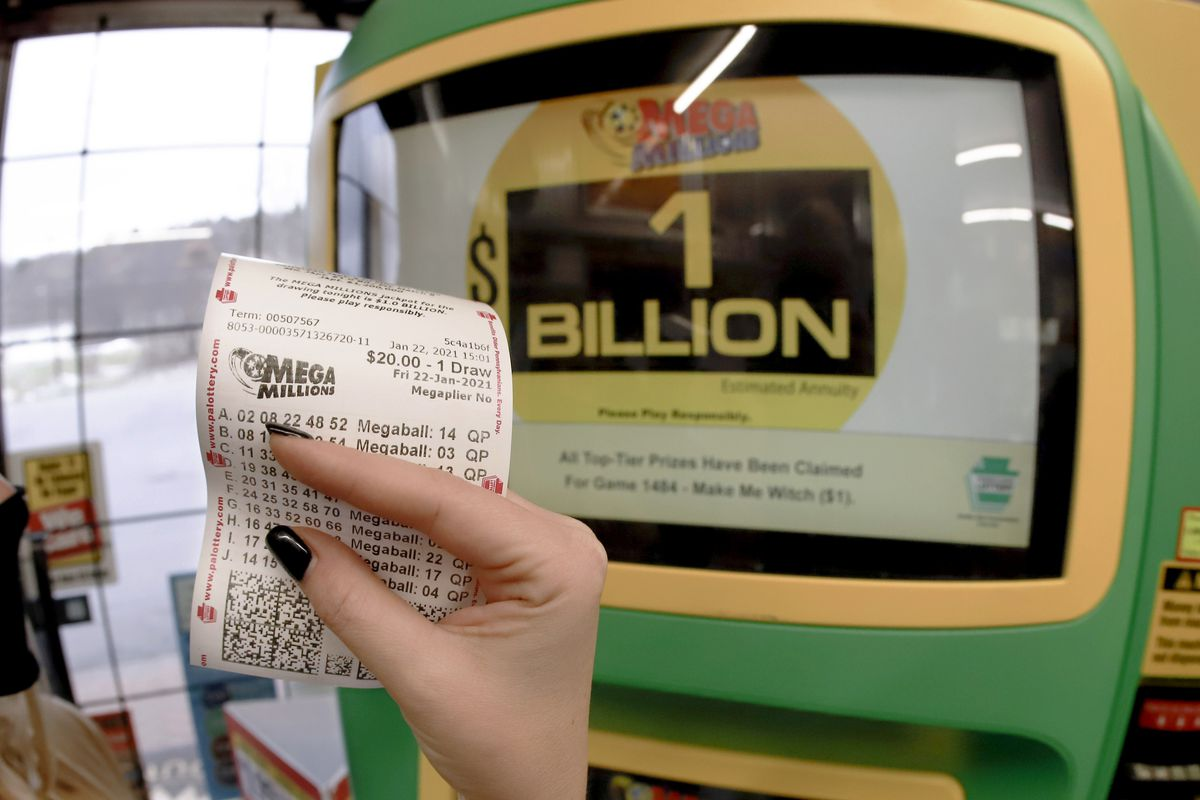 In this Jan. 22, 2021, file photo, a patron, who did not want to give her name, shows the ticket she had just bought for the Mega Millions lottery drawing at the lottery ticket vending kiosk in Cranberry Township, Pa.