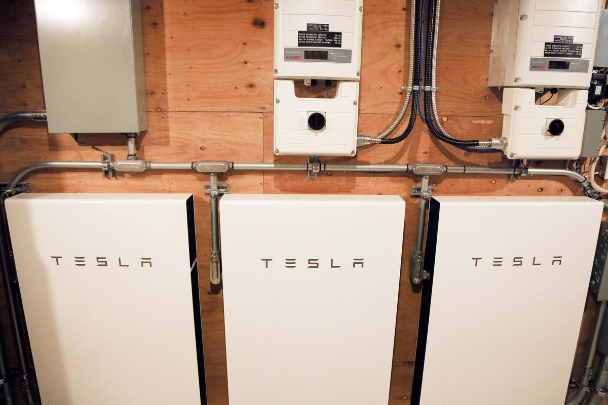A bank of Tesla batteries on a wall in a home's garage.