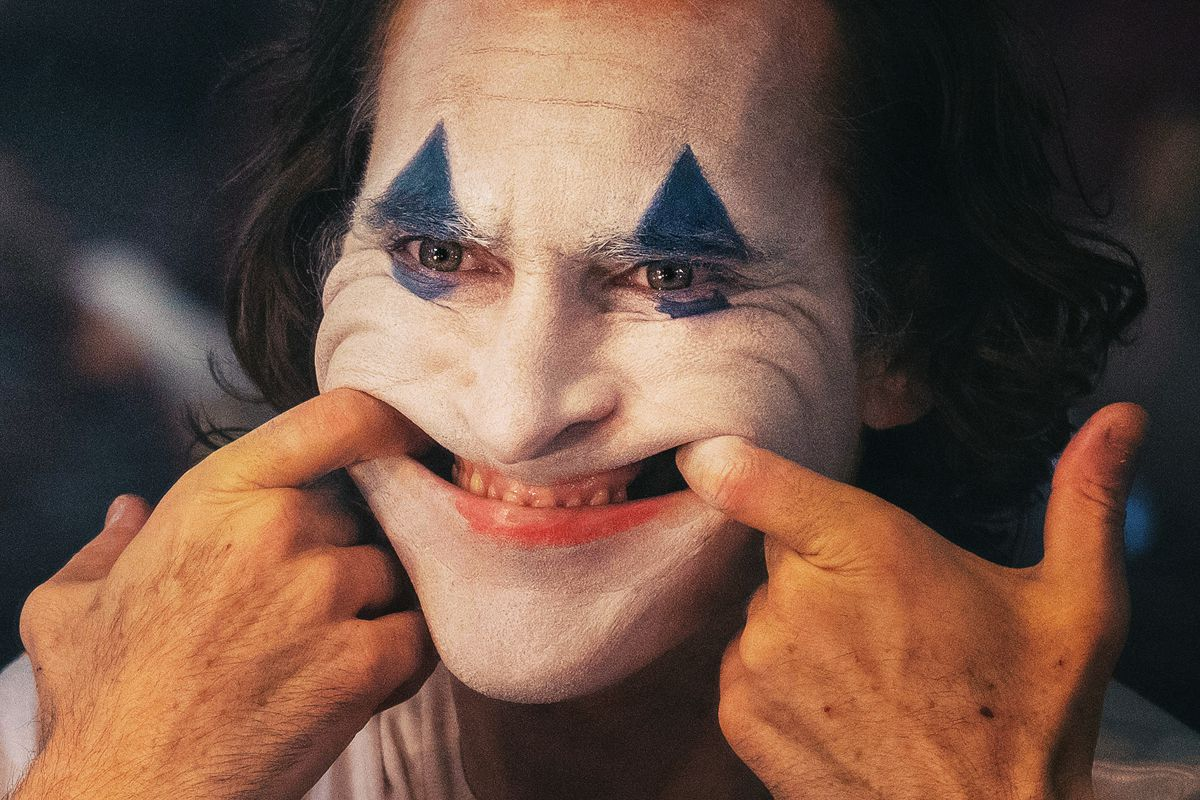 Joaquin Phoenix as the Joker pulls his mouth into a demonic grin