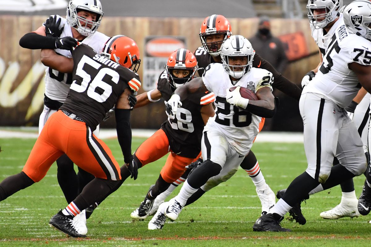 Las Vegas Raiders running back Josh Jacobs (28) runs through the Cleveland Browns defense during the first half at FirstEnergy Stadium.