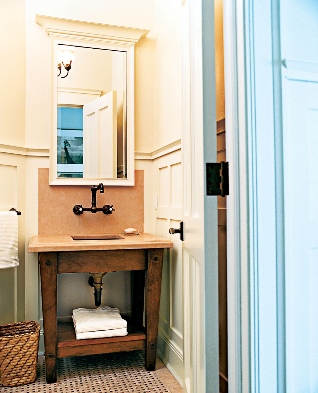 """<p><strong>Finely Crafted</strong><br> Wrapped in wainscoting that reflects the house's Craftsman feel, this half bath designed by architect Jay Haverson is """"furnished"""" with a solid oak vanity topped and backed with limestone, and an oil-rubbed bronze faucet by Rohl mounted on the wall.</p>"""