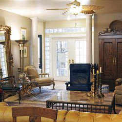 The living room includes a large mirror and tall columns. Eddy Rall and Patty Momenee point out that few items in the house were bought new; most of the furniture and fixtures were from garage sales, Habitat for Humanity's Re-Store, clearance sales or the curb.