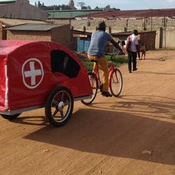 A Ride for Lives bike ambulance carries a passenger to a hospital in Uganda, where cars are scarce and thousands of people every year die trying to get to hospitals on foot.