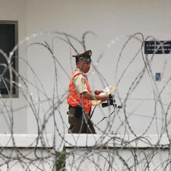 A security guard walks in the compound of the U.S. Embassy surrounded by barbed wire in Jakarta, Indonesia, Friday, Sept. 21, 2012. The U.S. has closed its diplomatic missions in Indonesia ahead of expected continuing protests over an anti-Islam film.