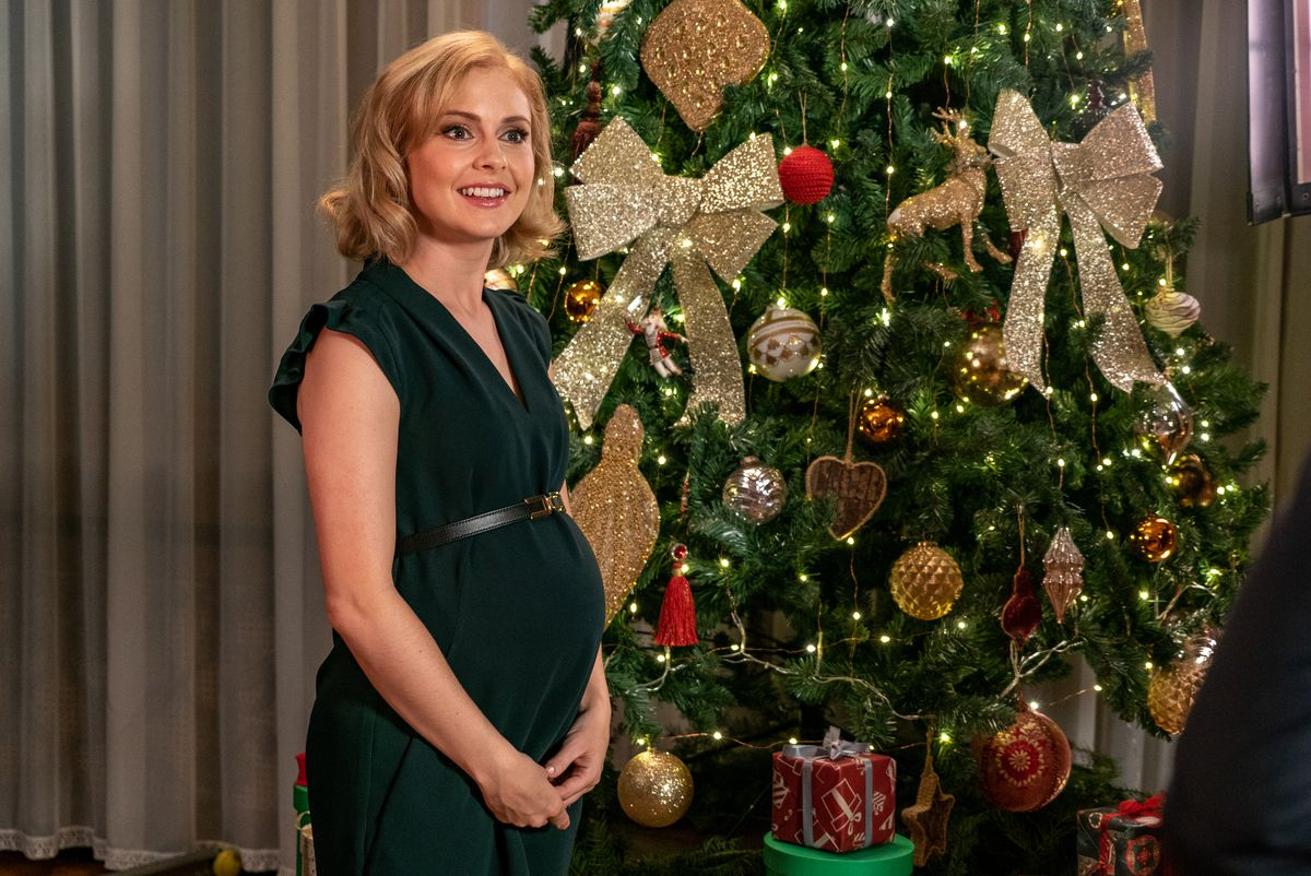 The Christmas princess from The Christmas Prince pregnant in front of a christmas tree