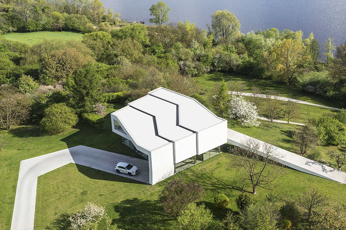 On an isolated swath of land in Poland, this home is wrapped in its own white concrete driveway, which extends down towards the pier and towards the road above. The home itself is wrapped three times, with the driveway peeling up from the ground to meet t