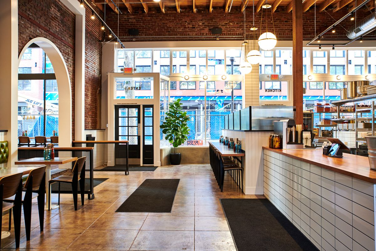 A picture of Bae's Chicken's front room, which uses white tile, exposed brick, and wood to create a warm feel
