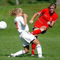 East High's Jane Nelson, right, kicks the ball by Lindsay Brough of Murray High in girls soccer action earlier this season. Murray won 1-0.
