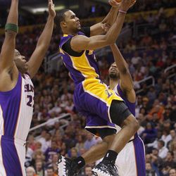 Los Angeles Lakers' Ramon Sessions drives past Phoneix Suns' Michael Redd, left, and Markieff Morris, right, during the first half of an NBA basketball game, Saturday, April 7, 2012, in Phoenix.
