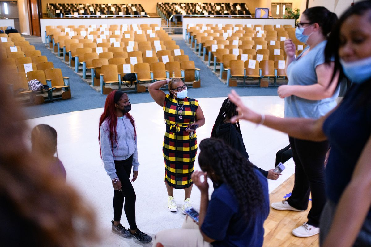 An adult wearing a multi-colored dress stands in front of students inside an auditorium.