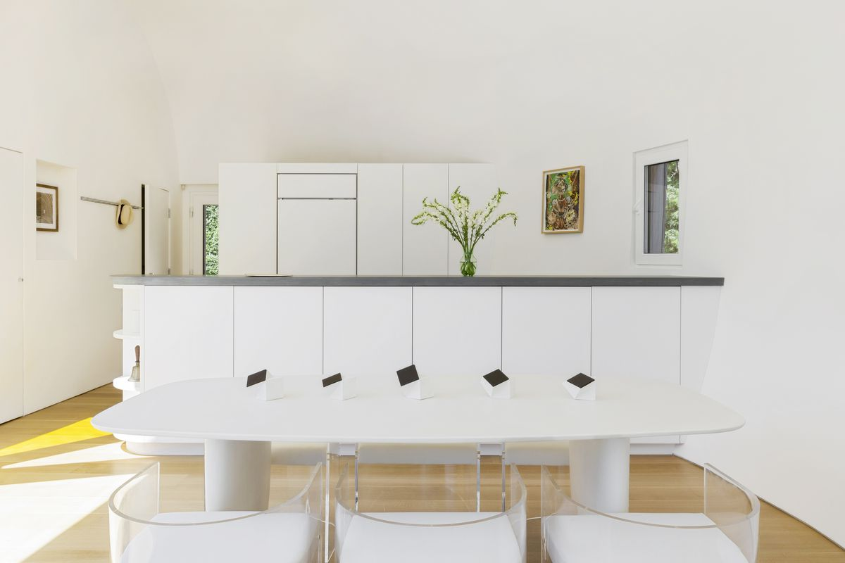 An all-white kitchen with white dining table, cabinets, and island.