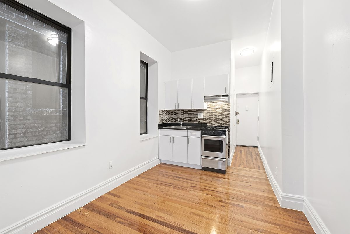 A small kitchen with a window and white cabinetry.