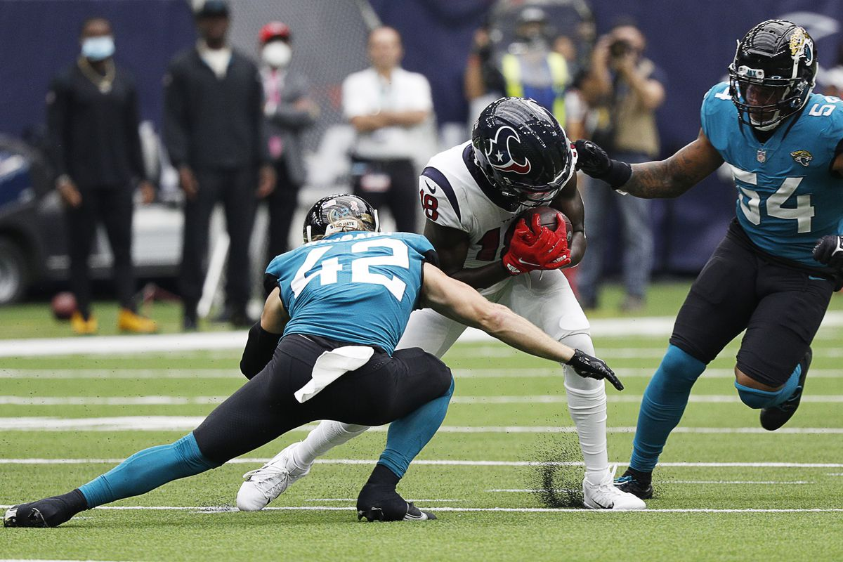 Chris Conley #18 of the Houston Texans is tackled by Damien Wilson #54 of the Jacksonville Jaguars and Andrew Wingard #42 at NRG Stadium on September 12, 2021 in Houston, Texas.