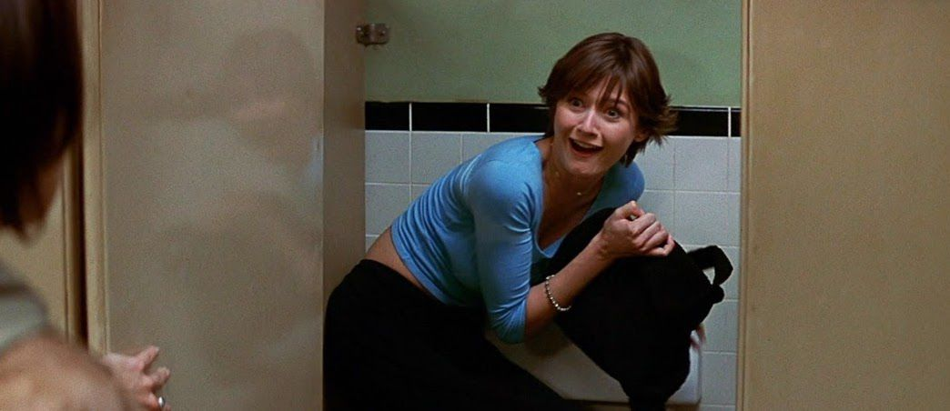 emily mortimer as angelina hides a purse in a toilet