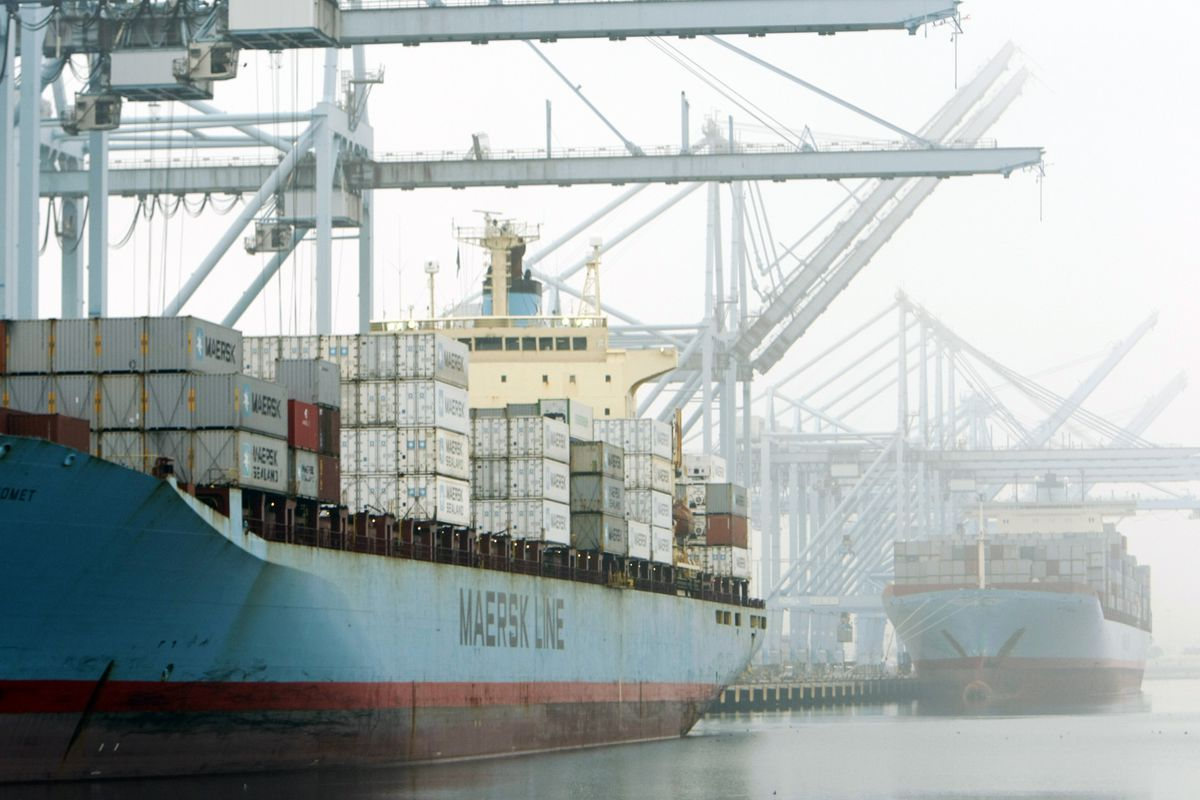 Cranes load shipping containers onto large ships amid fog in Los Angeles.