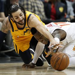 Utah Jazz's Ricky Rubio, of Spain, left, reaches for a loose ball against Atlanta Hawks' Dennis Schroder, of Germany, in the first quarter of an NBA basketball game in Atlanta, Monday, Jan. 22, 2018. (AP Photo/David Goldman)