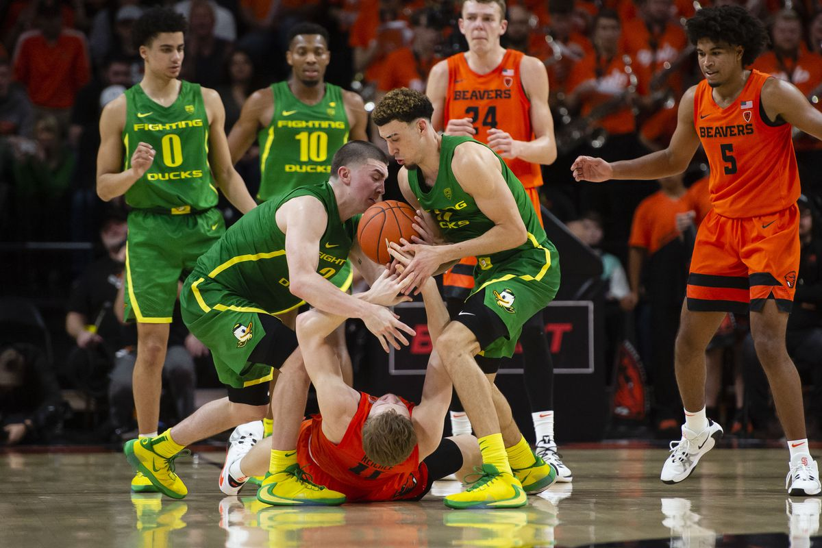 Oregon Ducks guard Payton Pritchard and guard Chris Duarte steal the ball away from Oregon State Beavers guard Zach Reichle (on floor) during the second half at Gill Coliseum.