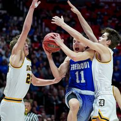 Davis' Rex Sunderland, right, is charged with the foul as Fremont's Tige Voorhees drives between him and Davis' Jax Pearce in the 6A boys basketball championship game at the Huntsman Center in Salt Lake City on Saturday, Feb. 29, 2020.