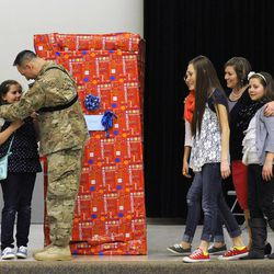 Air Force Tech Sgt. Edward Goettig hugs his daughter Olivia after she unwrapped her present on her 10th birthday to discover her dad inside, who returned home a week early prior to originally thought as sisters Bailee, Addie and Sydney join their mom, Tracie on stage at Fox Hollow Elementary School in Lehi on Thursday, March 6, 2014. Goettig had been deployed to Afghanistan since Aug. 27, 2013.