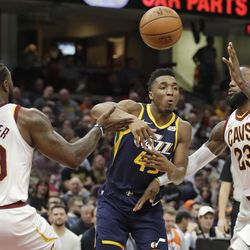 Utah Jazz's Donovan Mitchell (45) passes between Cleveland Cavaliers' Jae Crowder (99) and LeBron James (23) in the first half of an NBA basketball game, Saturday, Dec. 16, 2017, in Cleveland. (AP Photo/Tony Dejak)