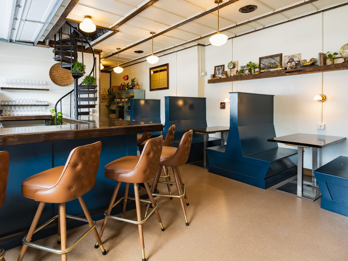 Leather high chairs around a navy bar.