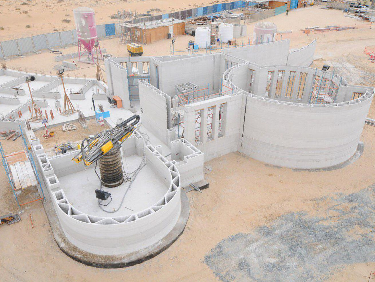 Building with two rounded sections under construction via machine extruding concrete mixture.