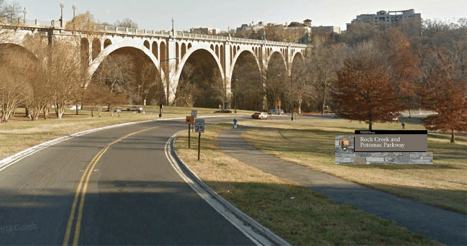 A two-lane road adjacent to a pedestrian/bike path. A rendering of a sign for a park is shown in the grass next to the path.