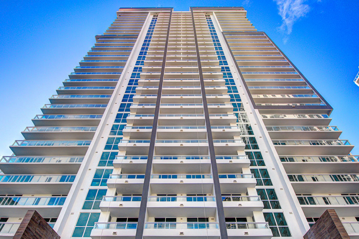 Street view looking up at the Bond on Brickell, a white tower with blue windows rising high into the clear sky